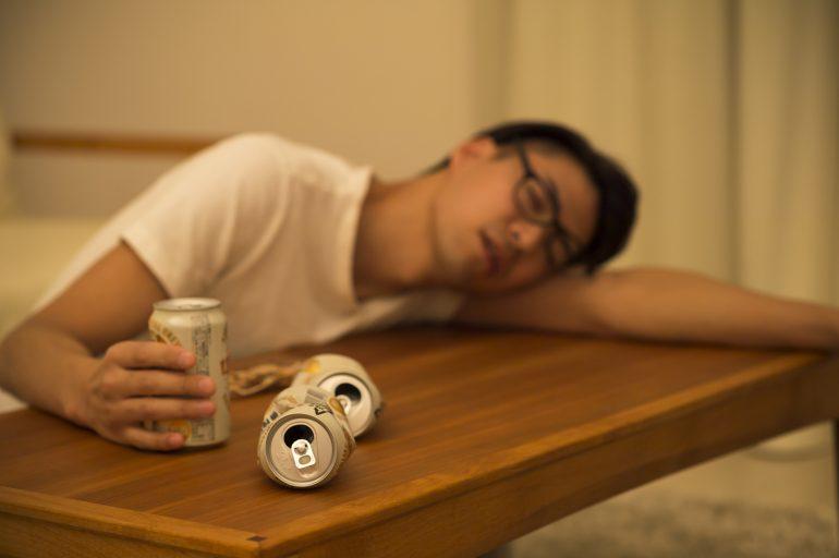 お酒を飲んで寝ている男性
