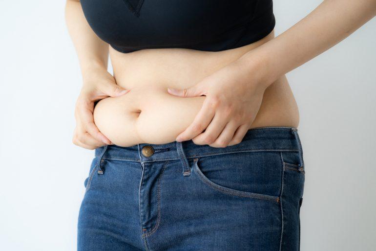 お腹の脂肪をつまんでいる女性